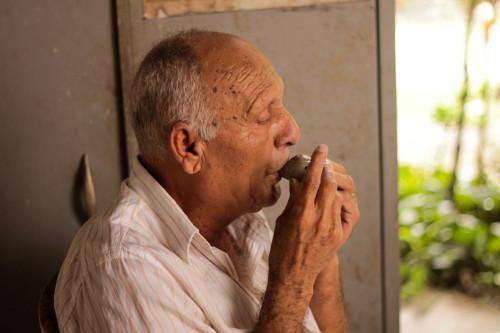 (Mestre Nado afina seus instrumentos de barro logo após serem moldados com água, ainda antes de eles irem para o forno.)