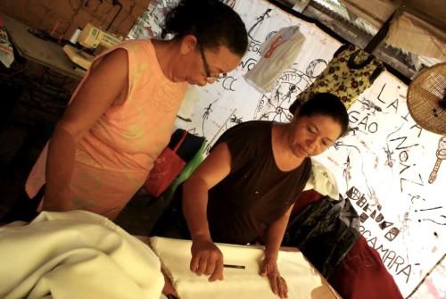 (Mestre Fátima e uma de suas aprendizes, em oficina de corte e costura. Foto de Curò Domenico.)